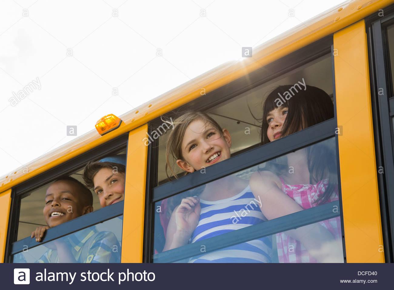 Smiling schoolchildren looking through bus window - Stock Image