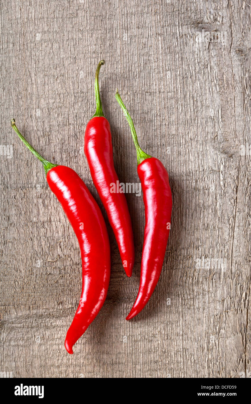 Red Chillies on Rustic Background - three red chillies on a plank or rustic background. - Stock Image