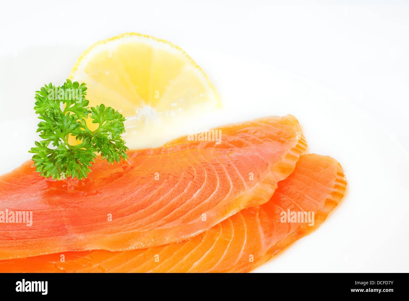 Smoked Salmon - cold smoked salmon on a plate with parsley and lemon. - Stock Image