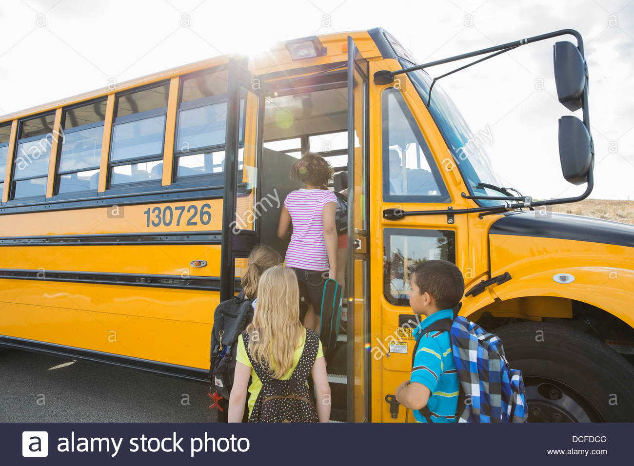 Schoolchildren boarding school bus going for field trip - Stock Image