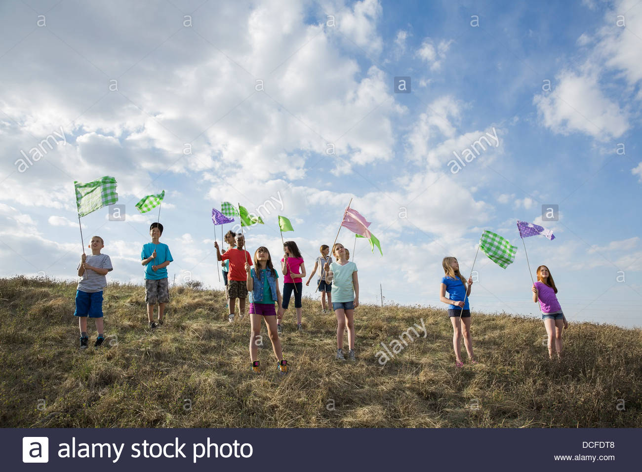 Schoolchildren holding flags on a hill - Stock Image