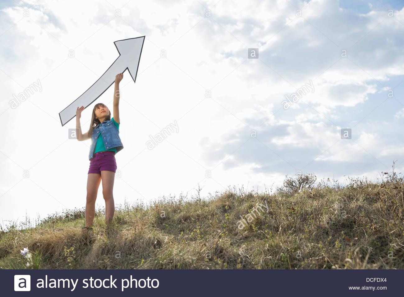 Schoolgirl holding upward arrow outdoors - Stock Image