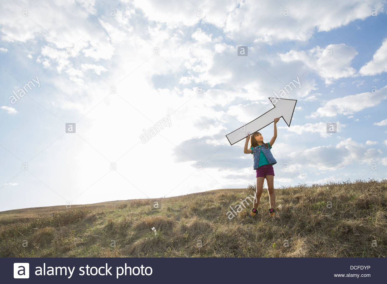 Schoolgirl holding upward arrow on hillside - Stock Image