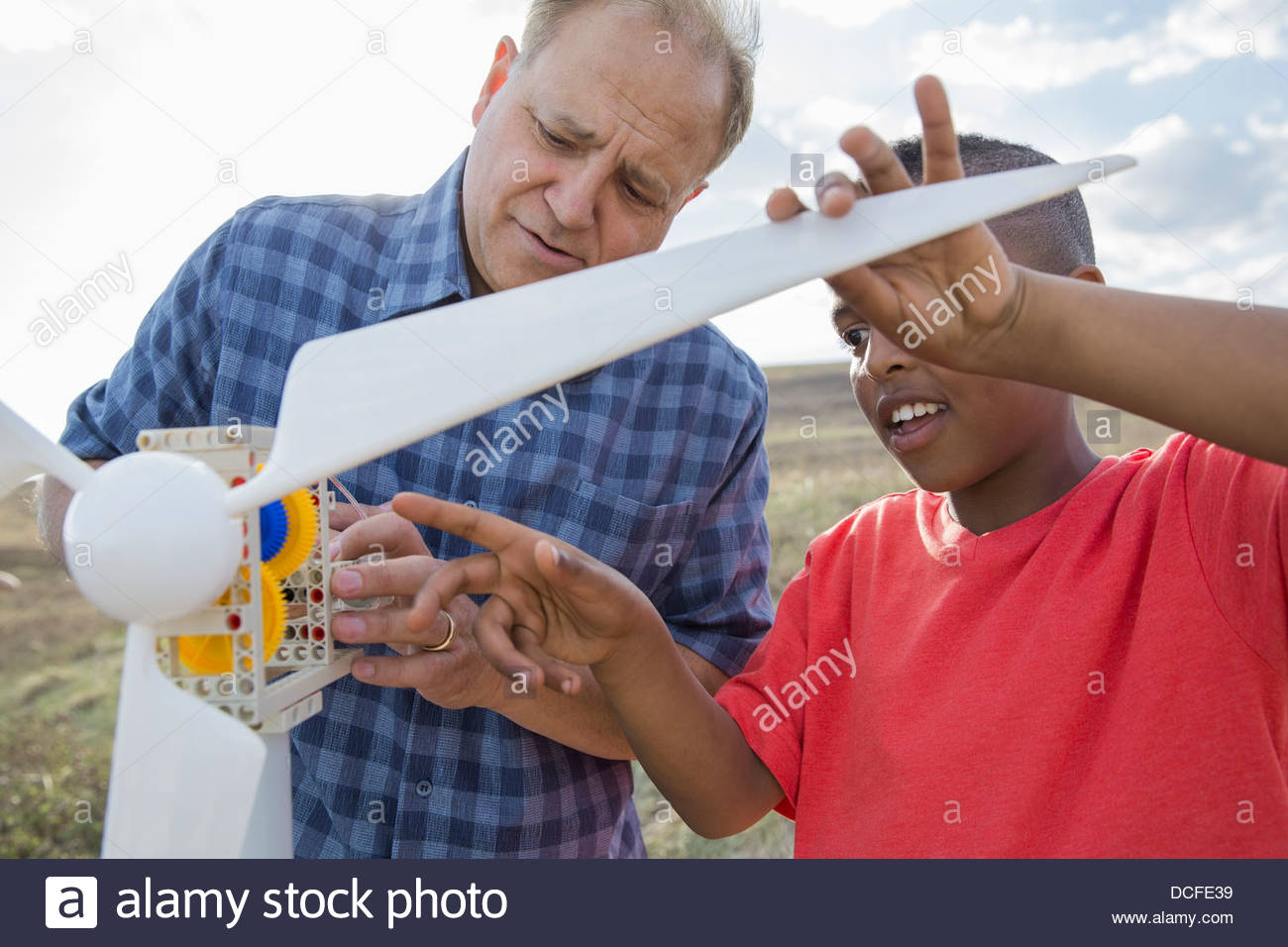 Man explaining wind turbine to schoolboy - Stock Image
