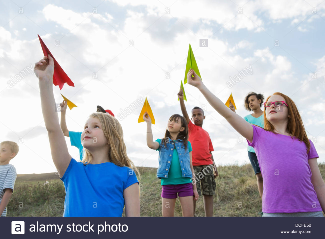 Schoolchildren aiming paper airplanes on field - Stock Image