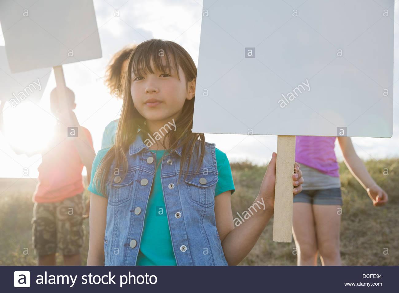 Portrait of cute girl holding blank billboard - Stock Image
