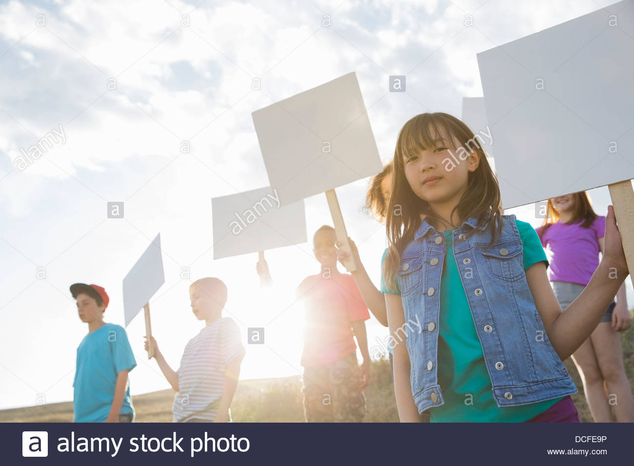 Portrait of girl holding blank billboard with friends during field trip - Stock Image