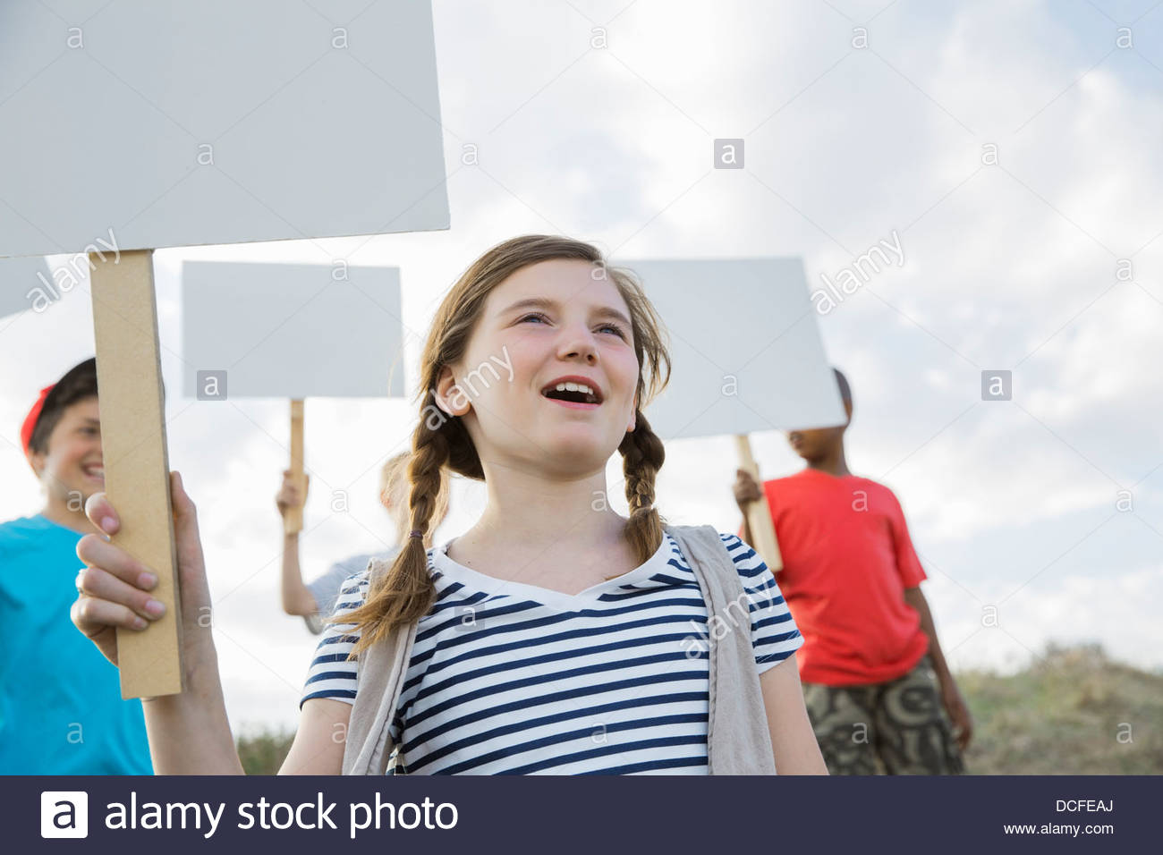 Cute girl holding blank billboard outdoors - Stock Image
