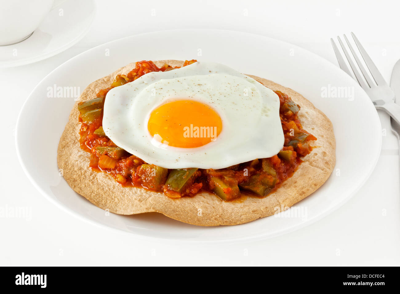 Huevos Rancheros - Mexican style breakfast of a tortilla, topped with salsa ranchera and a free range fried egg. - Stock Image