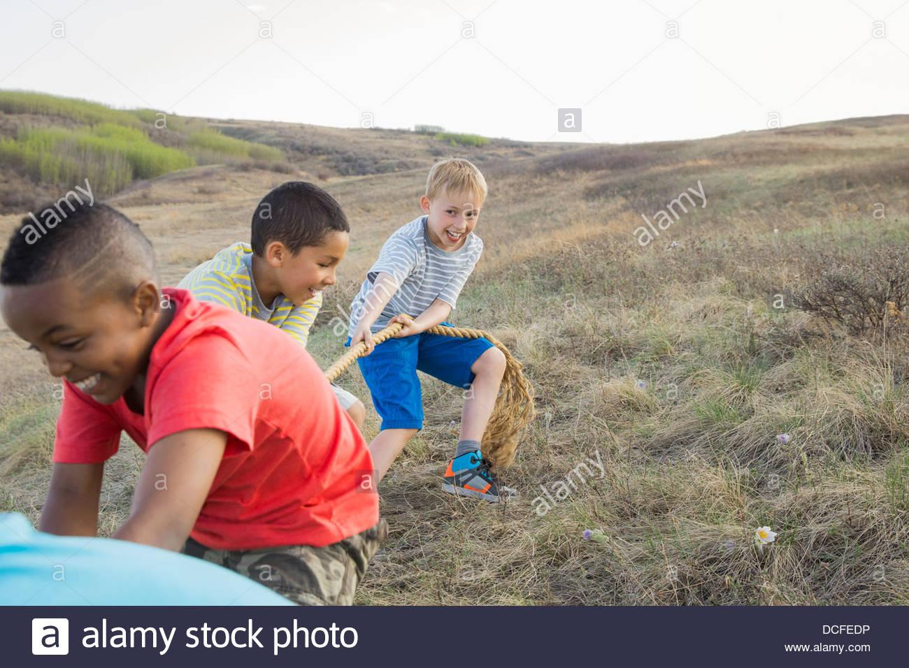 Schoolboys playing tug-of-war - Stock Image