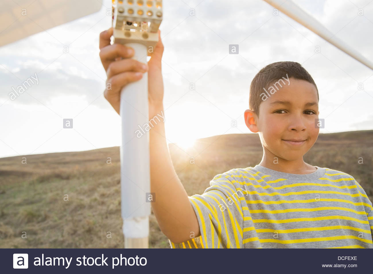 Portrait of boy holding wind turbine model - Stock Image