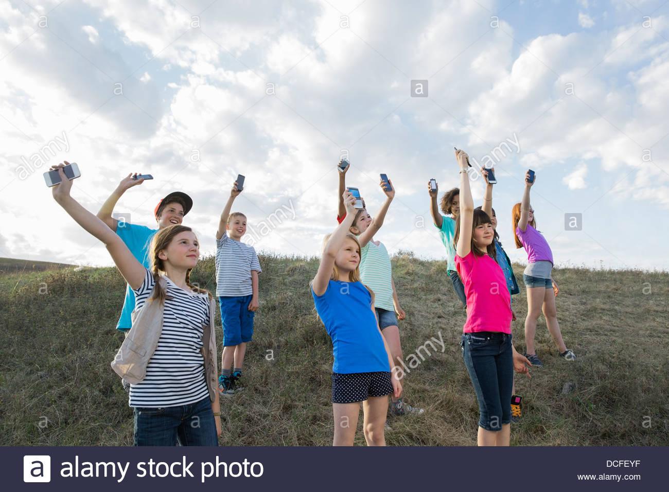 Schoolchildren holding mobile phones up - Stock Image