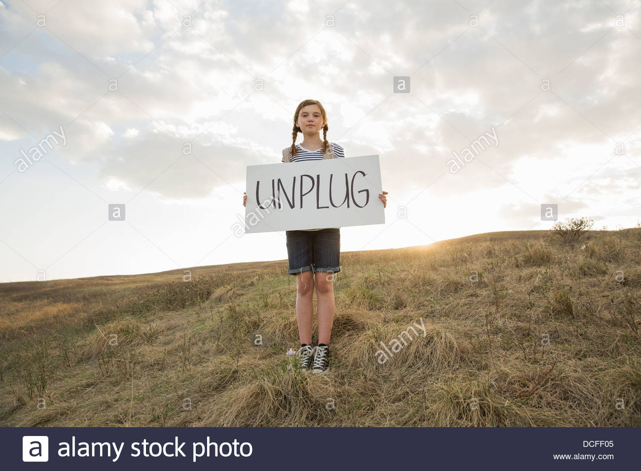 Girl holding unplug sign on hillside - Stock Image