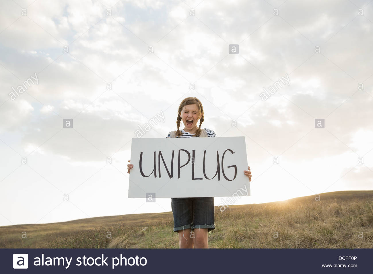 Girl making a statement with unplug sign on hillside - Stock Image