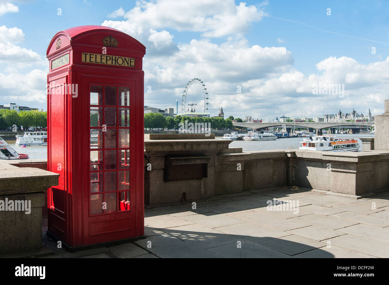 Red telephone box next to the river Thames, London, England - Stock Image