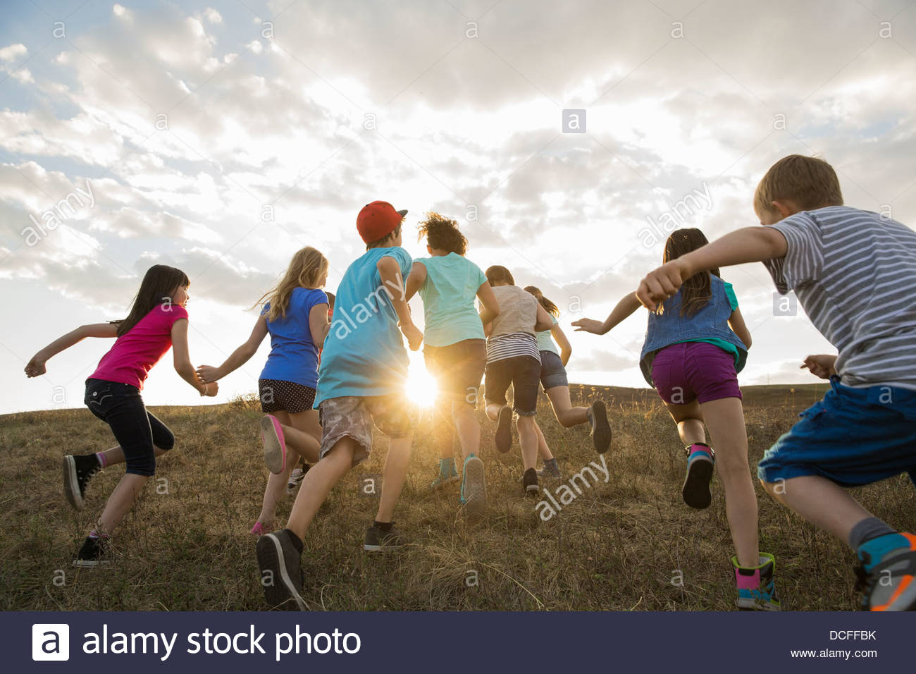 Rear view of children running uphill - Stock Image