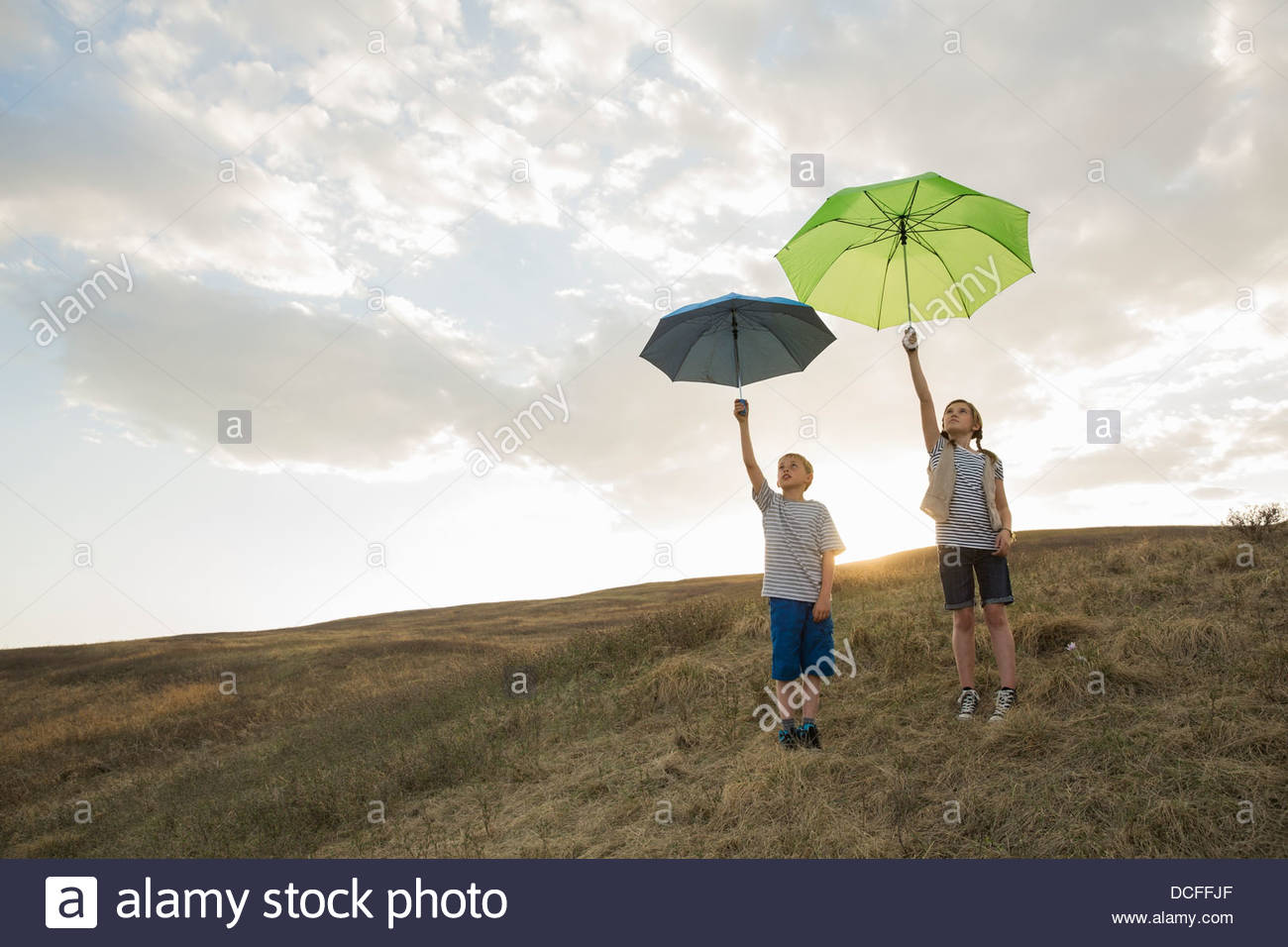 Kids holding umbrellas up to the sky - Stock Image
