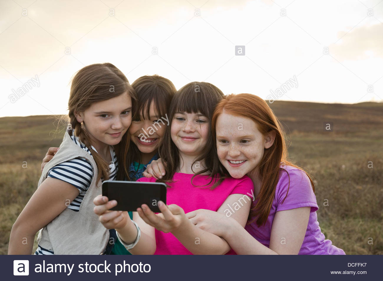 Smiling schoolgirls taking self-portrait outdoors - Stock Image