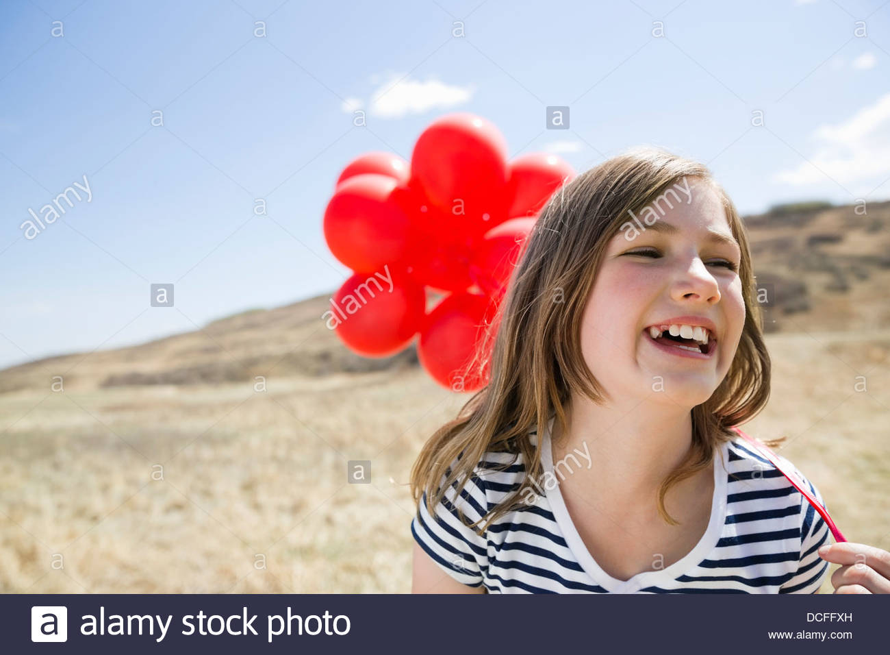 Smiling girl holding red balloons outdoors - Stock Image