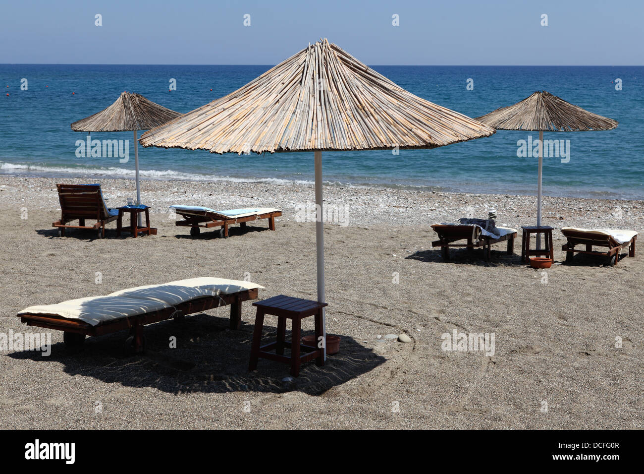 Sunloungers with sunshades at Lardos Beach near Lindos, Rhodes, Greece. - Stock Image