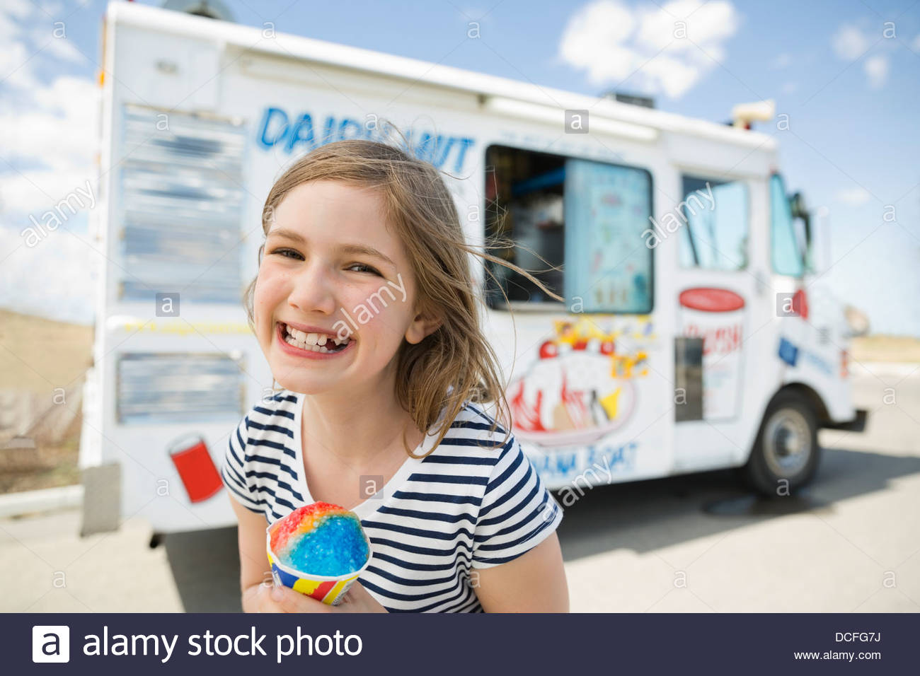 Portrait of smiling girl holding snow cone - Stock Image