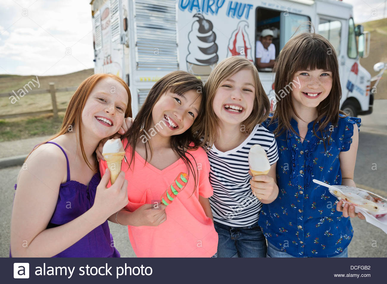 Portrait of cheerful little girls holding frozen treats - Stock Image