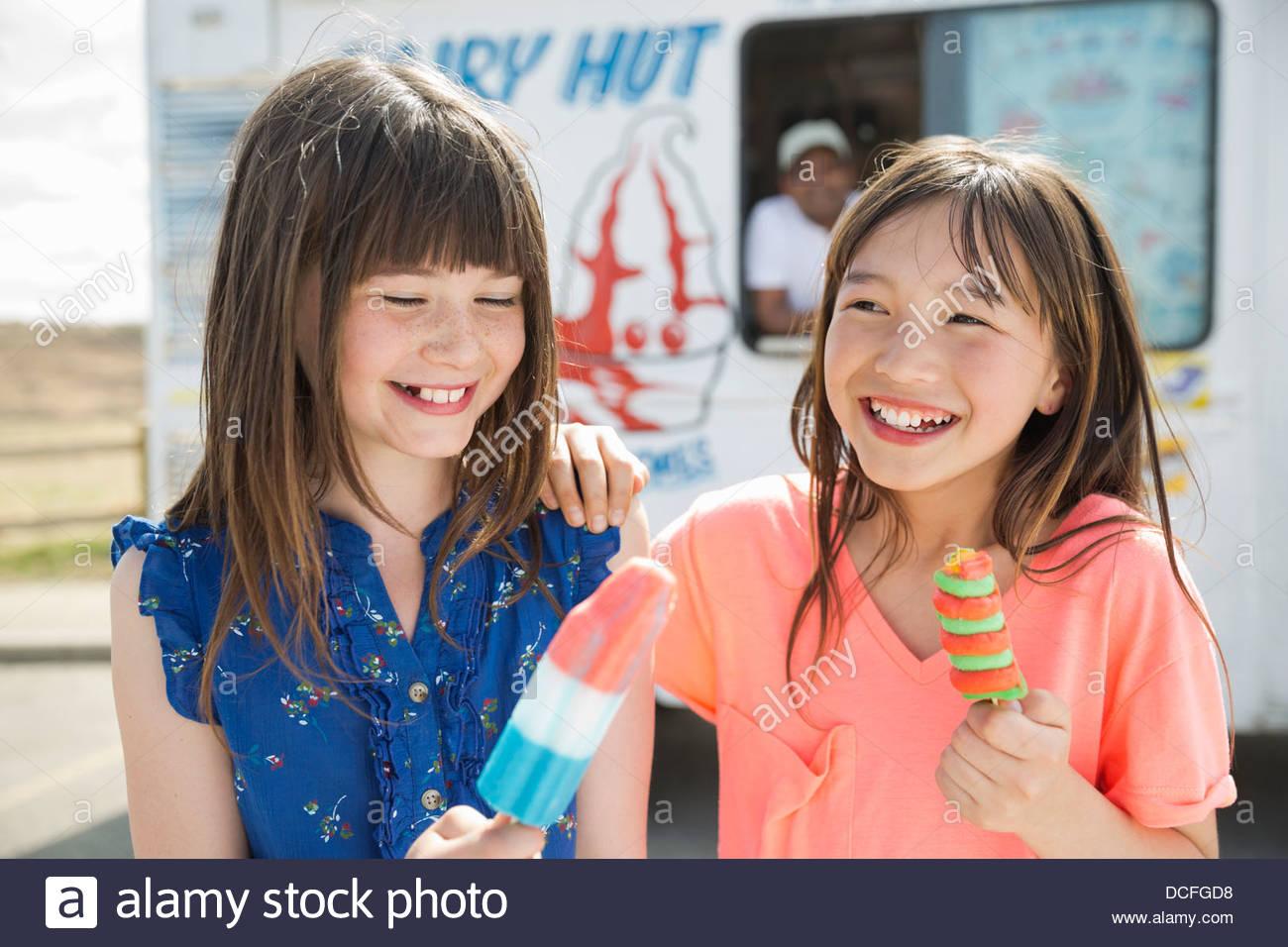 Girls eating popsicles outside - Stock Image