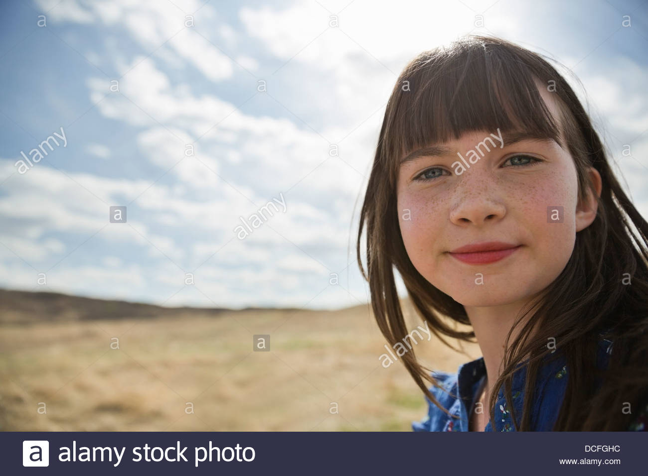Portrait of cute schoolgirl looking at camera - Stock Image