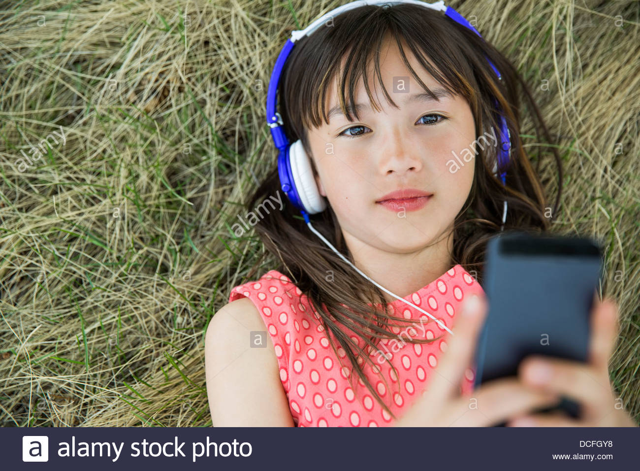 Girl lying down listening to headphones - Stock Image