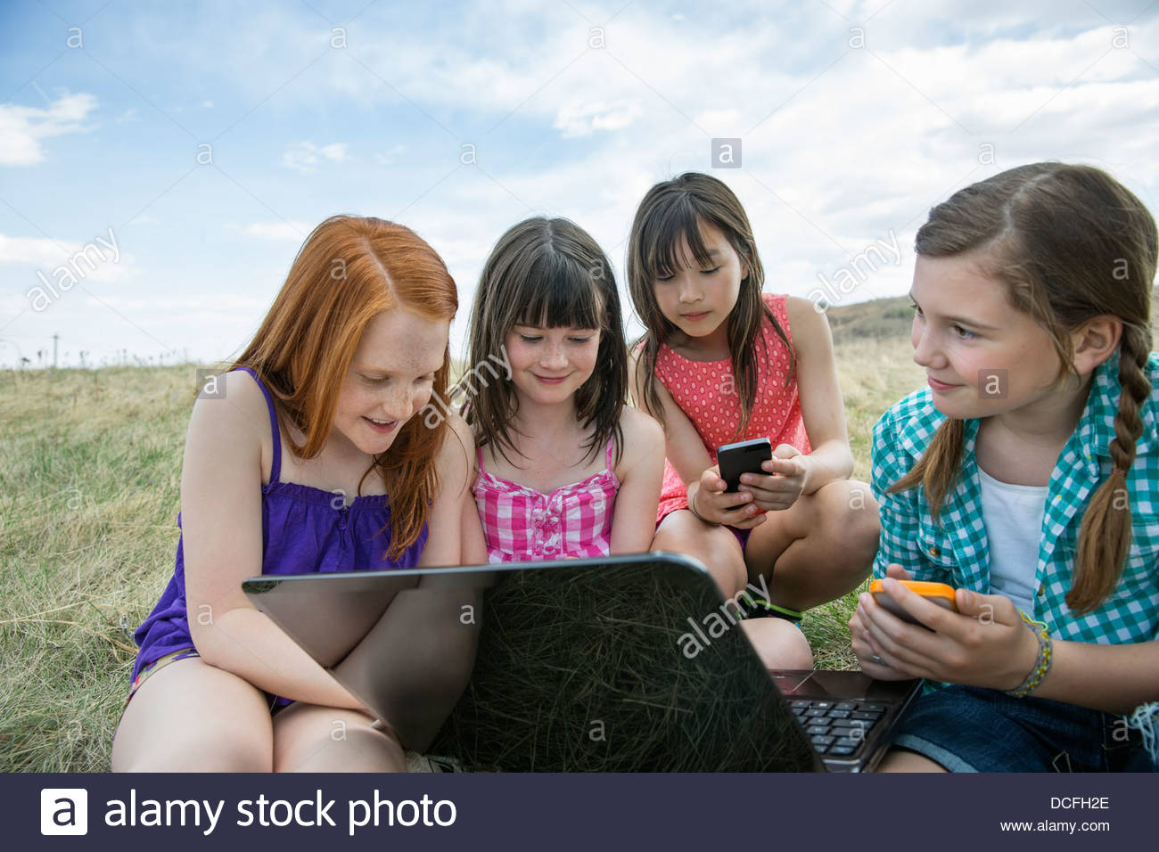 Schoolgirls with smart devices sitting outdoors - Stock Image
