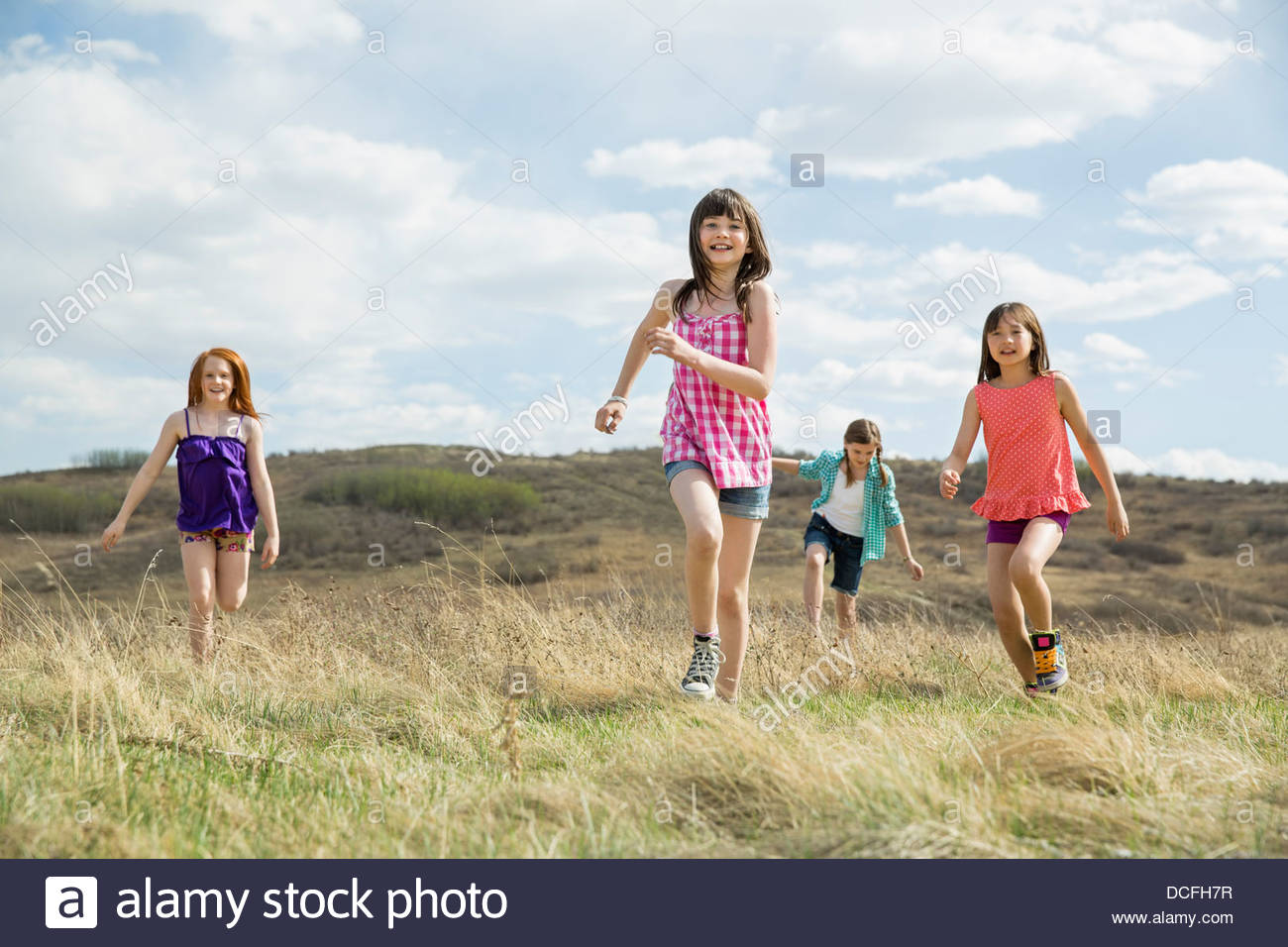 Young girls running through field - Stock Image