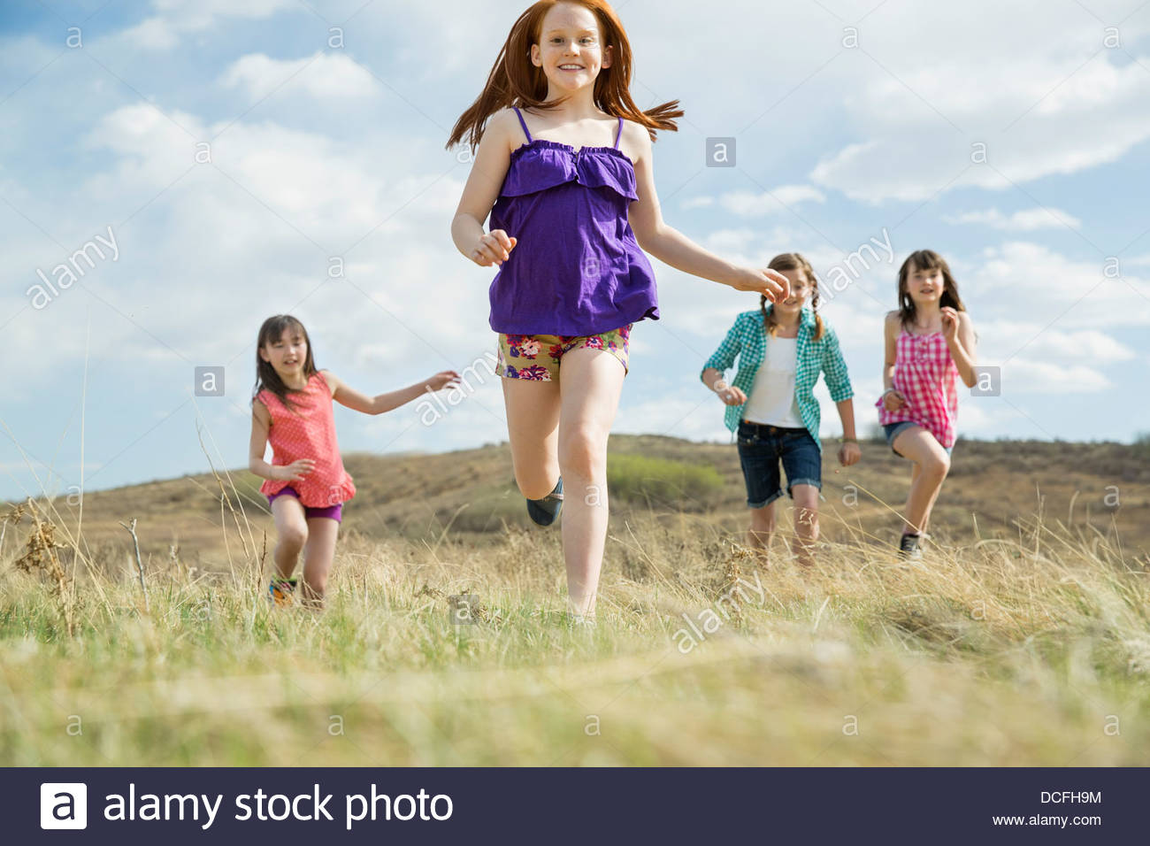 Cheerful schoolgirls running on field - Stock Image