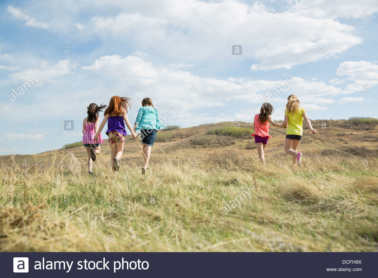 Rear view of girls walking outdoors - Stock Image