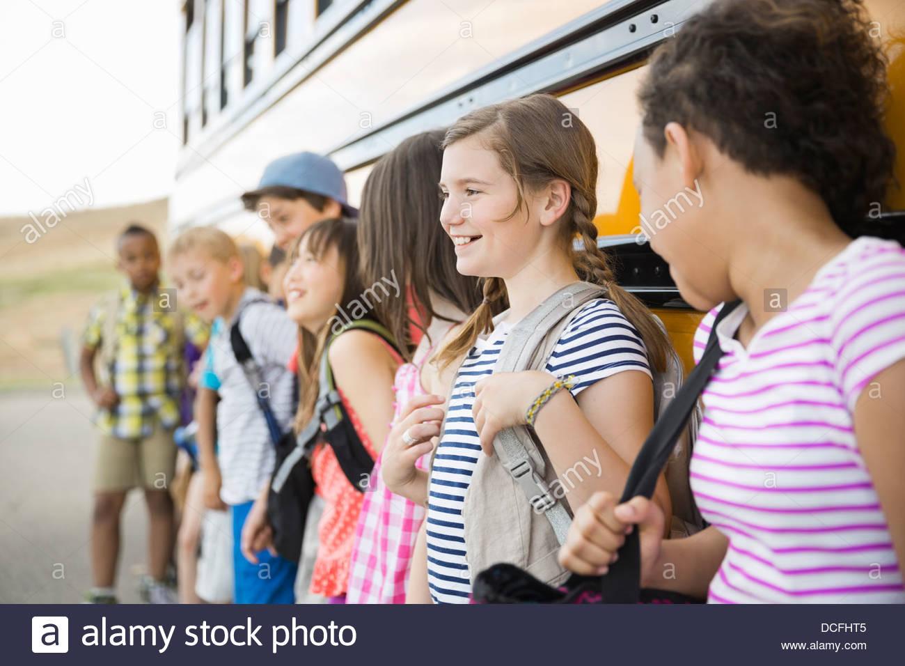 Schoolchildren standing against school bus - Stock Image