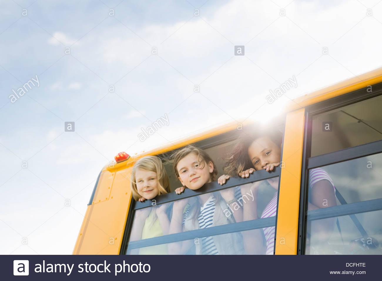 Portrait of schoolgirls looking out of school bus windows - Stock Image