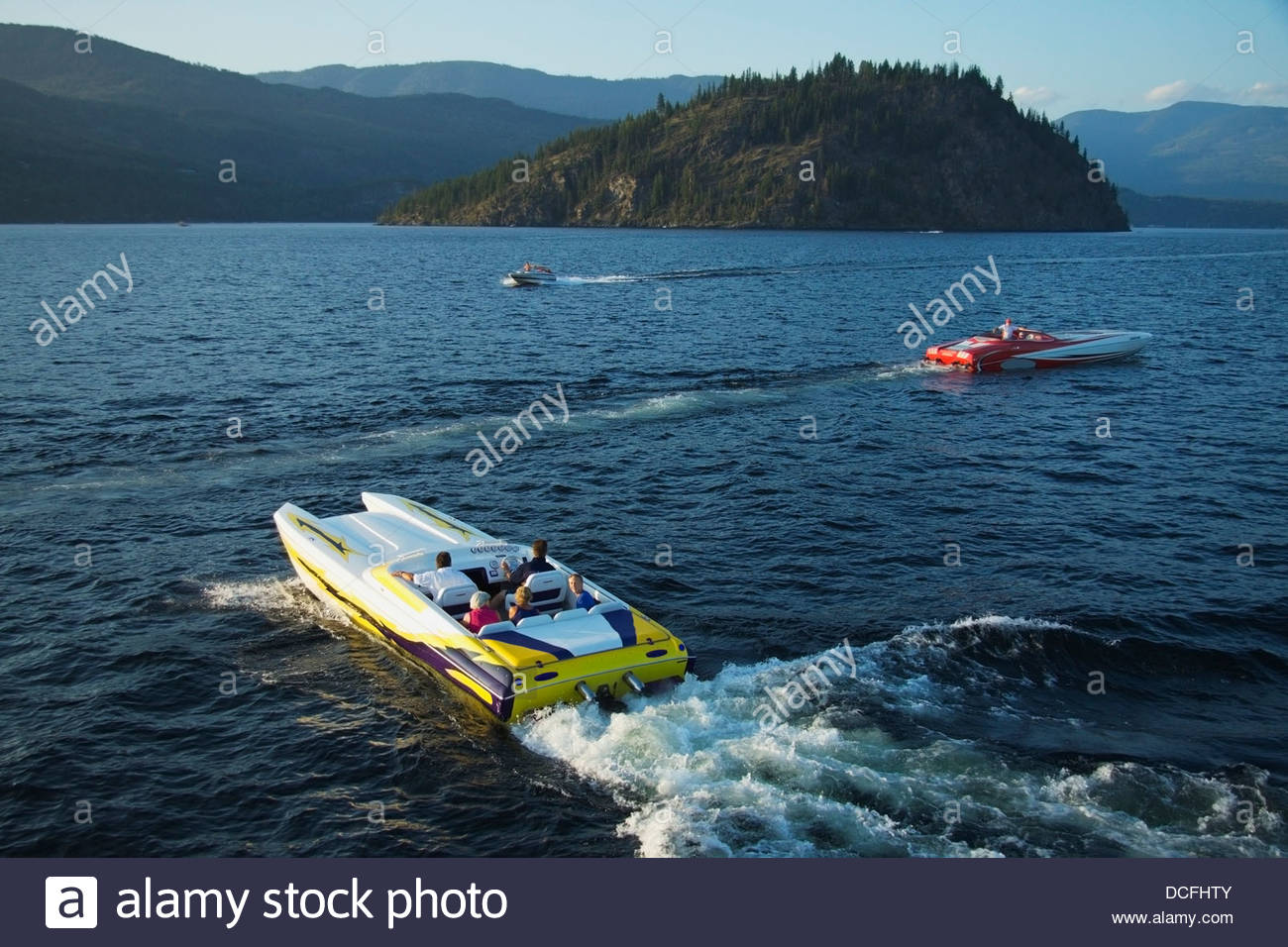 Three Go-Fast Boats With Tourists On Shuswap Lake Going Past Copper Island;British Columbia Canada Stock Photo