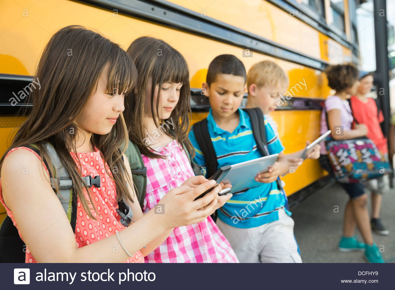 Schoolchildren using smart devices while waiting - Stock Image