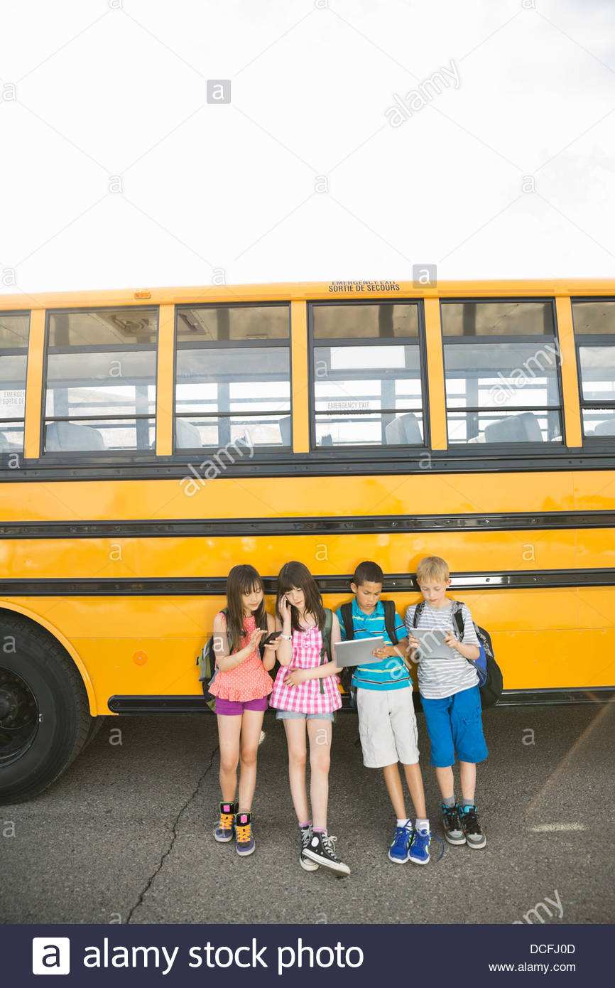 Schoolchildren using smart devices while waiting by school bus - Stock Image