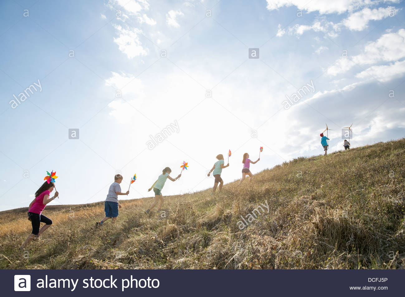 Kids walking up hill with pinwheels and wind turbine models - Stock Image