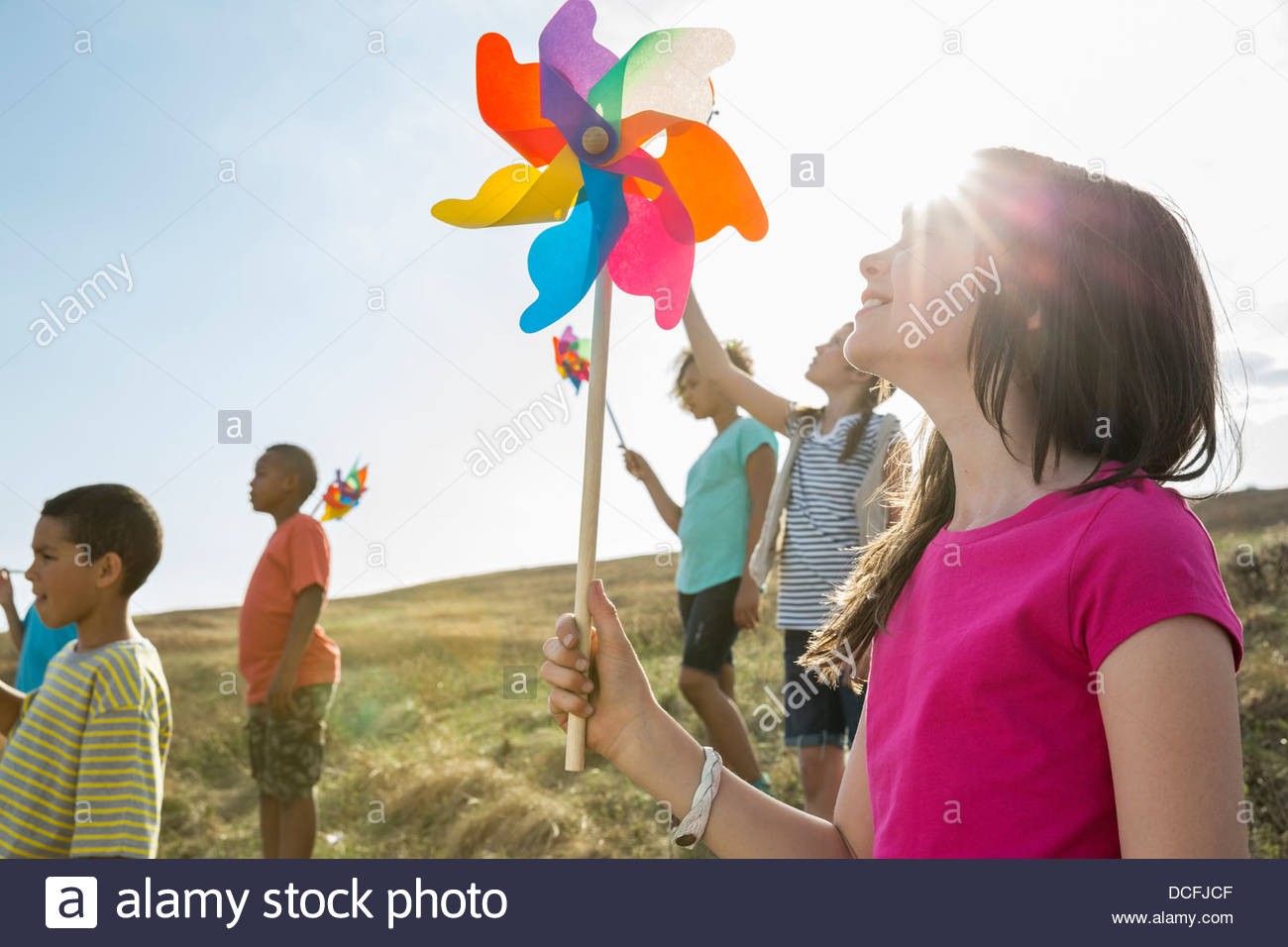 Schoolchildren holding pinwheels up outdoors - Stock Image