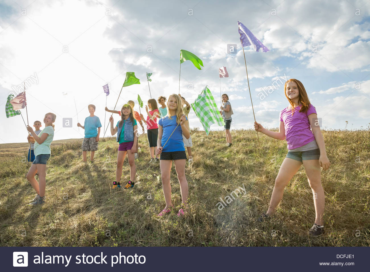 Group of kids holding flags up on a hill - Stock Image