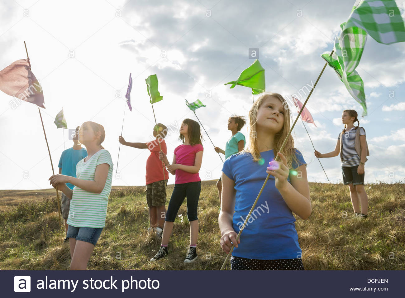 Schoolchildren looking up at flags - Stock Image
