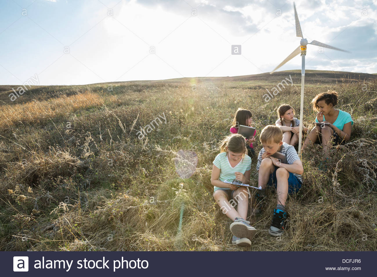 Schoolchildren discussing notes on wind turbine model - Stock Image
