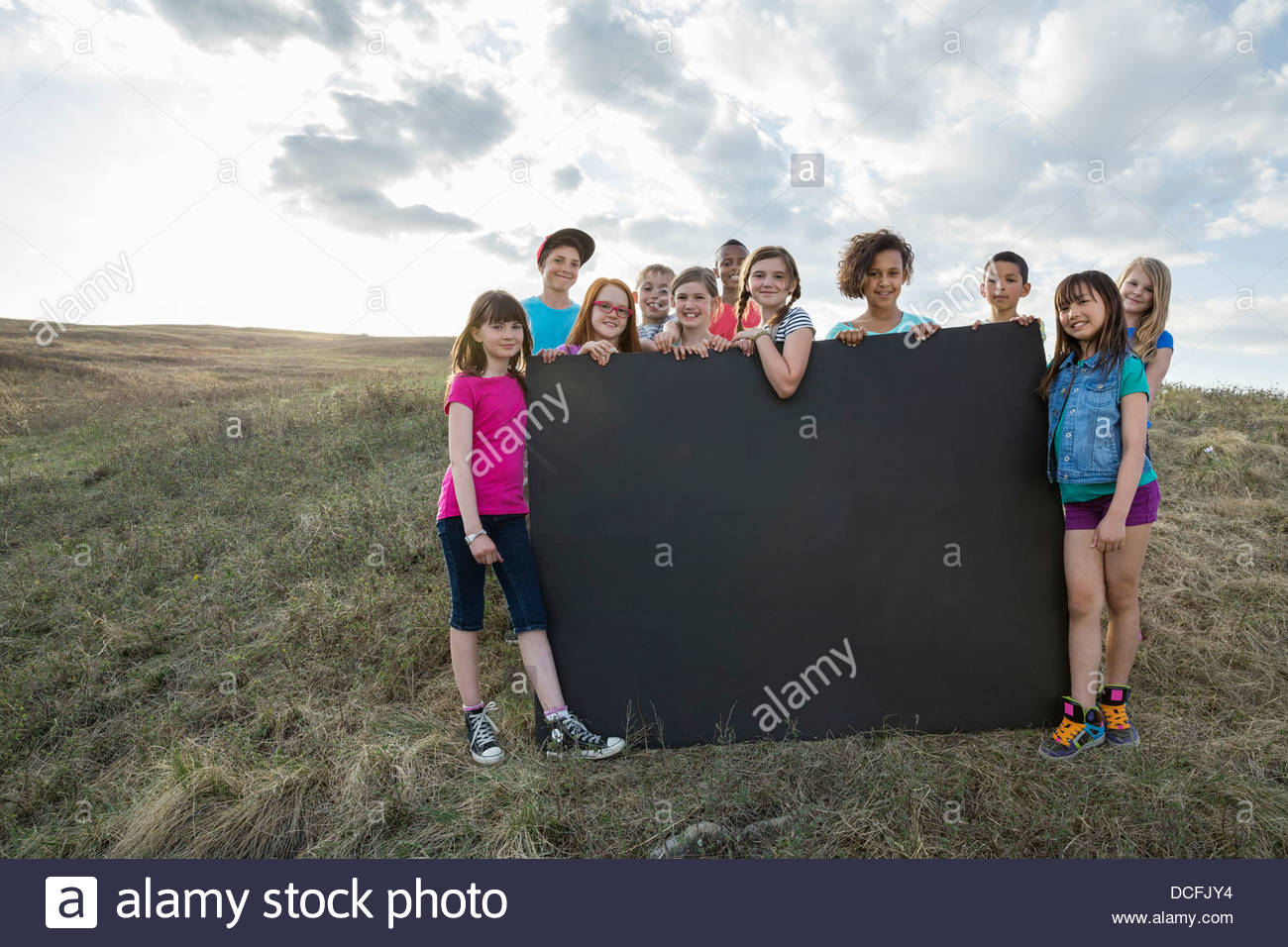Group of kids outdoors holding blank sign board - Stock Image