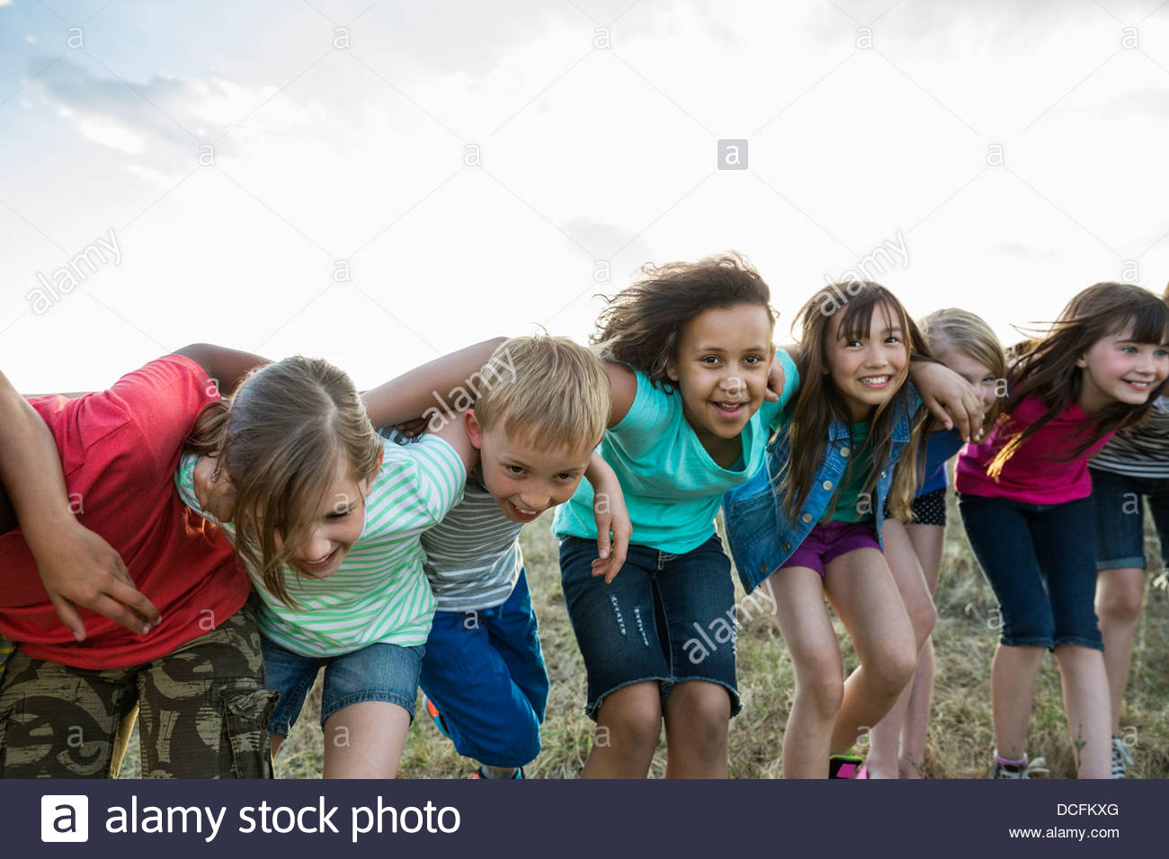 Group portrait of smiling kids standing in a row - Stock Image