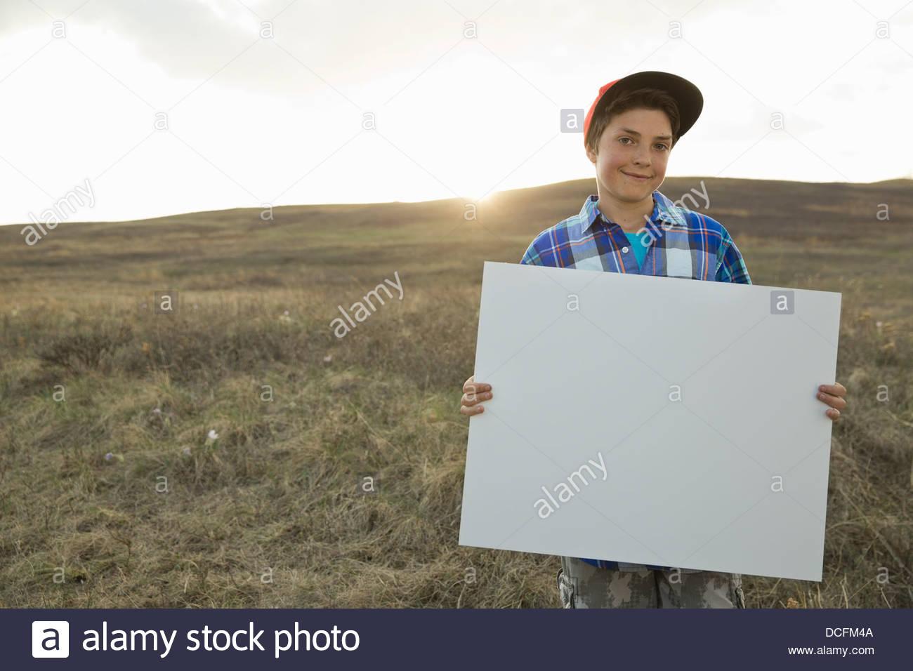 Boy standing on hillside holding blank sign board - Stock Image