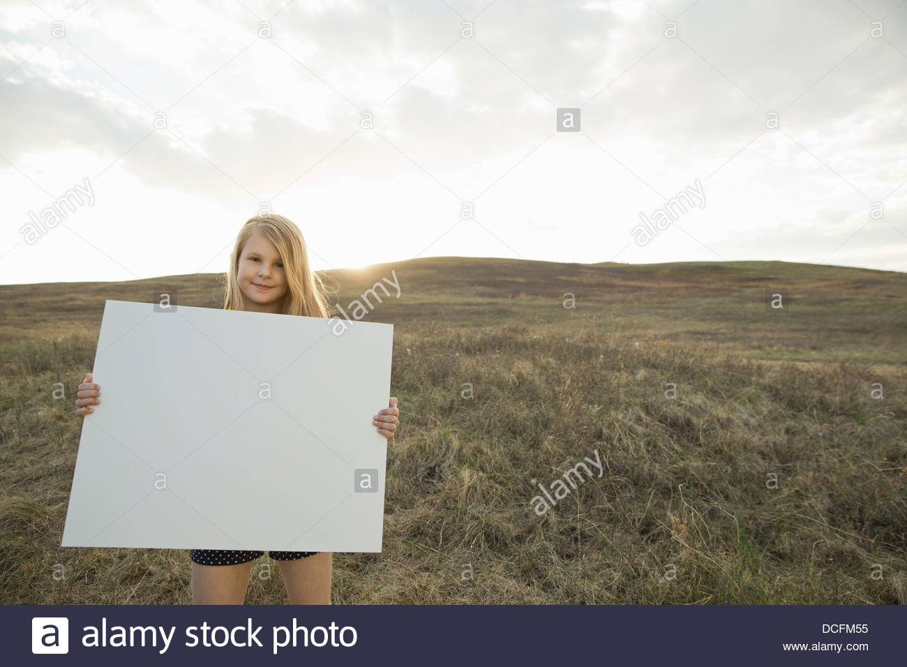 Girl standing on hillside holding sign board - Stock Image