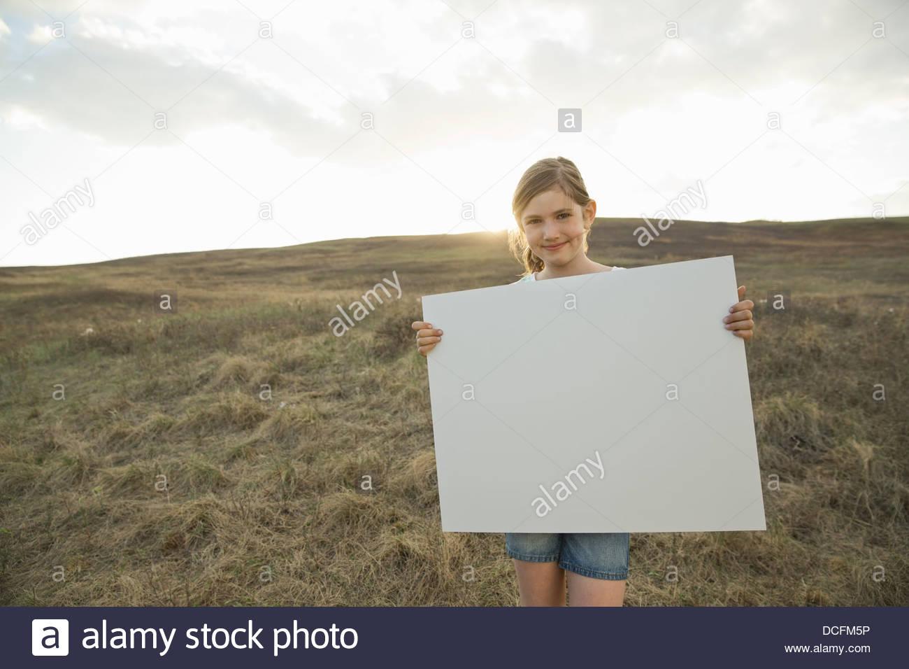 Portrait of smiling girl on hillside holding blank sign board - Stock Image