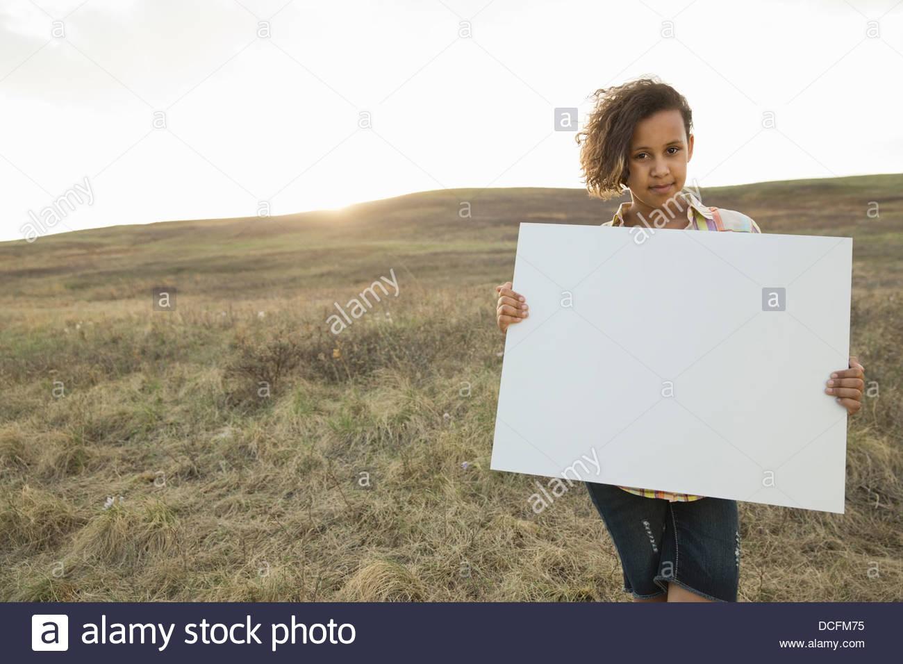 Portrait of girl on hillside holding blank sign board - Stock Image