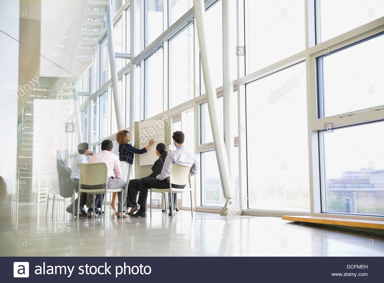 Business woman presenting to colleagues - Stock Image